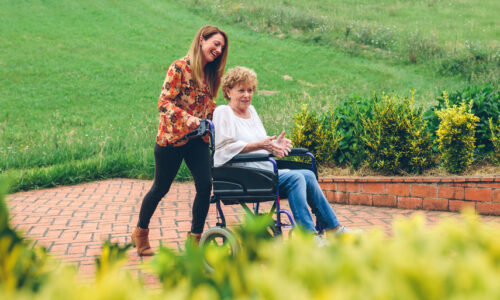Live-In-care. Woman being pushed in wheelchair in a garden