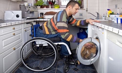 Young man in wheelchair using washing machine - supported living services